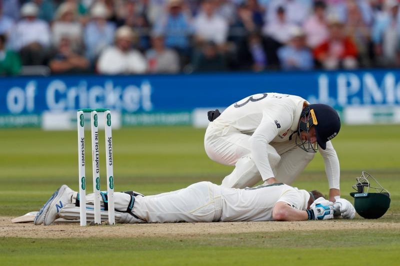 TOPSHOT - England's Jos Buttler shows concern for Australia's Steve Smith as he falls to the pitch after being hit on the neck by a ball off the bowling of England's Jofra Archer (unseen) during play on the fourth day of the second Ashes cricket Test match between England and Australia at Lord's Cricket Ground in London on August 17, 2019. (Photo by Adrian DENNIS / AFP) / RESTRICTED TO EDITORIAL USE. NO ASSOCIATION WITH DIRECT COMPETITOR OF SPONSOR, PARTNER, OR SUPPLIER OF THE ECB (Photo credit should read ADRIAN DENNIS/AFP/Getty Images)