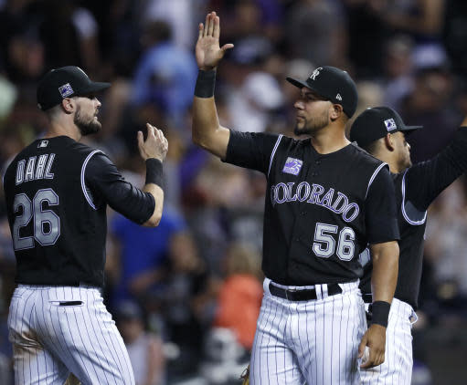 Colorado Rockies' Noel Cuevas, right, is congratulated by right fielder David Dahl after the Rockies defeated the Cincinnati Reds 5-4 in a baseball game Friday, May 25, 2018, in Denver. (AP Photo/David Zalubowski)
