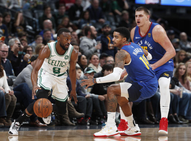 Boston Celtics guard Kemba Walker, left, is defended by Denver Nuggets guard Gary Harris and center Nikola Jokic, right, during the first half of an NBA basketball game Friday, Nov. 22, 2019, in Denver. (AP Photo/David Zalubowski)