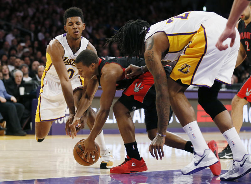 Toronto Raptors' Kyle Lowry, center, reaches for a loose ball between Los Angeles Lakers' Nick Young, left, and Jordan Hill, right, during the first half of an NBA basketball game in Los Angeles, Sunday, Dec. 8, 2013. (AP Photo/Danny Moloshok)
