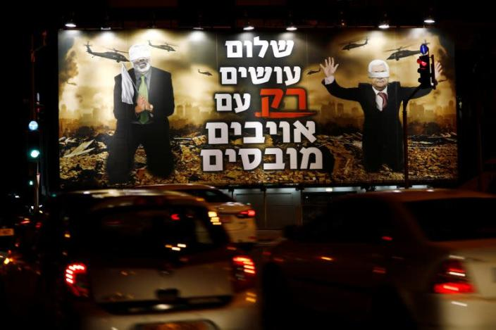 """A billboard over a Tel Aviv highway shows photo-shopped warzone images of Palestinian President Mahmoud Abbas and Hamas leader Ismail Haniyeh, both blindfolded, with the slogan read in Hebrew """"Peace is Made ONLY with Defeated Enemies\"""
