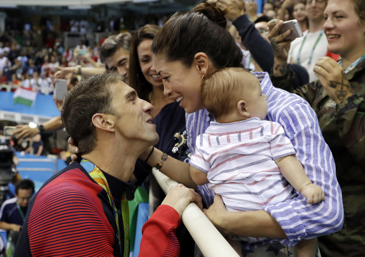 "FILE - In this Aug. 9, 2016, file photo, United States' swimmer Michael Phelps celebrates winning his gold medal in the men's 200-meter butterfly with his fiance Nicole Johnson and baby Boomer during the swimming competitions at the 2016 Summer Olympics in Rio de Janeiro, Brazil. Phelps says he has ""no desire"" to return to competitive swimming, but he's eager to stay involved with the sport and cheer on those who follow in his enormous wake. (AP Photo/Matt Slocum, File)"