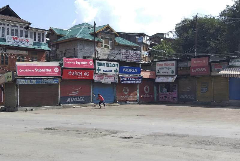 A Kashmiri plays cricket in a deserted area during curfew in Srinagar, Indian controlled Kashmir, Thursday, Aug. 8, 2019. The lives of millions in India's only Muslim-majority region have been upended since the latest, and most serious, crackdown followed a decision by New Delhi to revoke the special status of Jammu and Kashmir and downgrade the Himalayan region from statehood to a territory. Kashmir is claimed in full by both India and Pakistan, and rebels have been fighting Indian rule in the portion it administers for decades. (AP Photo/Sheikh Saaliq)