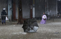 A woman helplessly watches her umbrella fly away in the wind during a heavy rain in Mumbai, India, Monday, May 17, 2021. Cyclone Tauktae, roaring in the Arabian Sea was moving toward India's western coast on Monday as authorities tried to evacuate hundreds of thousands of people and suspended COVID-19 vaccinations in one state. (AP Photo/Rajanish Kakade)