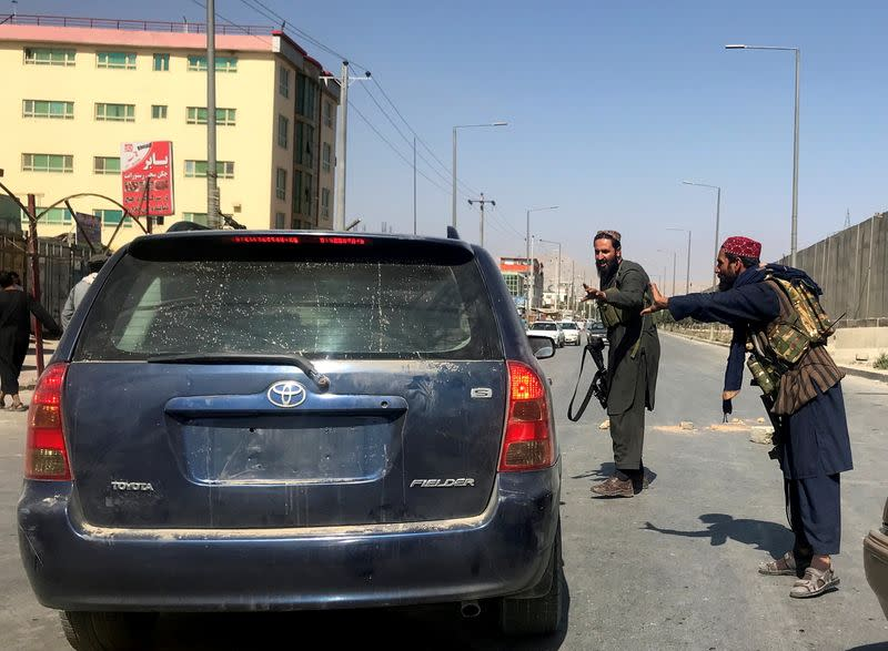 FILE PHOTO: Members of Taliban forces gesture as they check a vehicle in Kabul