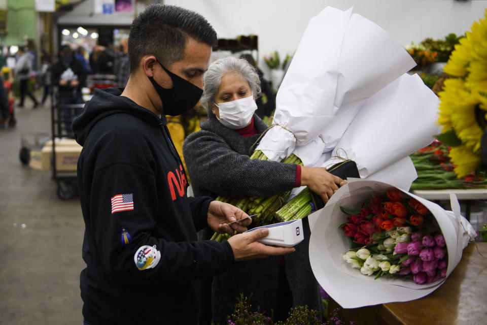 Jorge Olivera (L) of Stems Floral uses a Square Inc. credit card reader for a customer as they buy flowers ahead of the Valentine's Day holiday at the Southern California Flower Market on February 12, 2021 in Los Angeles, California. - While some florists note an increased demand for socially distant gifts, the Covid-19 pandemic has impacted global supply chains and shut down most large events including weddings where flowers are popular. The Valentine's Day and Mother's Day holidays are historically the two busiest days of the year for floral businesses. (Photo by Patrick T. FALLON / AFP) (Photo by PATRICK T. FALLON/AFP via Getty Images)