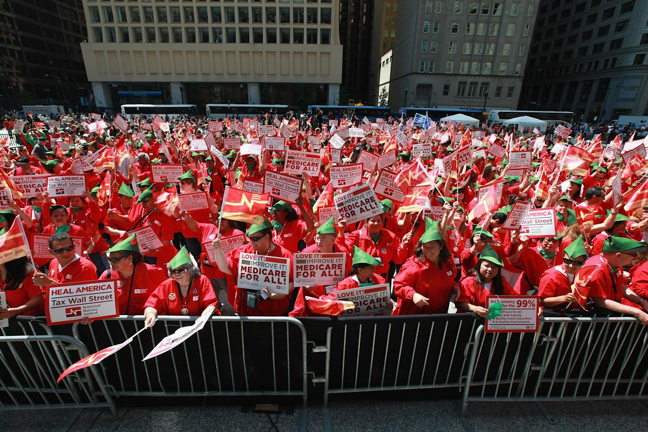 """Member of National Nurses United gather with other protestors rally in Daley Plaza calling for a """"Robin Hood"""" tax on stocks, bonds, derivatives and other financial instruments May 18, 2012 in Chicago, Illinois. This was the fifth day of protests in what is expected to be a full week of demonstrations as the city prepares to host the NATO Summit May 20-21. (Photo by Scott Olson/Getty Images)"""