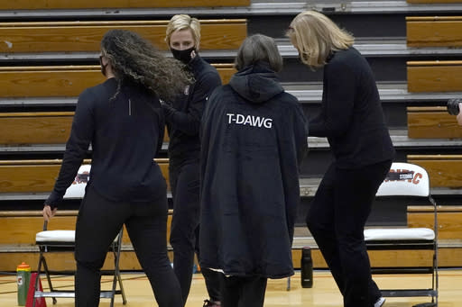 """Stanford coach Tara VanDerveer, center, wears an overcoat with """"T-DAWG"""" on the back that was given to her from her team after Stanford's 104-61 win over Pacific in an NCAA college basketball game made her the winningest coach in women's basketball history, Tuesday, Dec. 15, 2020, in Stockton, Calif. VanDerveer passed the late Pat Summitt with her 1,099 victory. (AP Photo/Rich Pedroncelli)"""