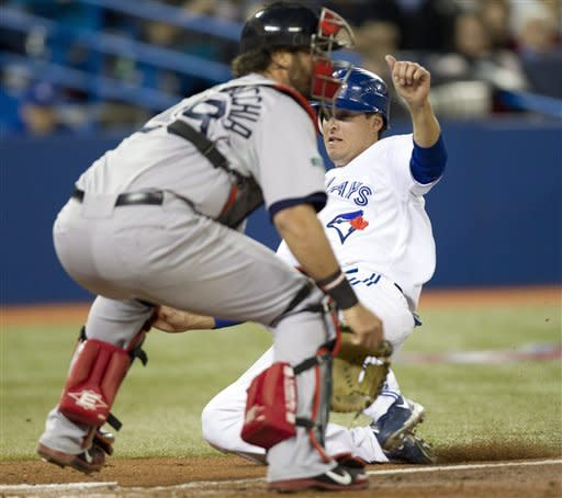 Toronto Blue Jays' Kelly Johnson, right, slides in to score behind Boston Red Sox catcher Jarrod Saltalamacchia during the third inning of a baseball game in Toronto on Tuesday, April 10, 2012. (AP Photo/The Canadian Press, Frank Gunn)