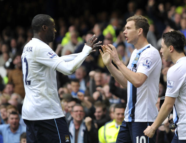 Manchester City's Edin Dzeko, right, celebrates with teammate Yaya Toure after scoring during their English Premier League soccer match against Everton at Goodison Park in Liverpool, England, Saturday May 3, 2014. (AP Photo/Clint Hughes)