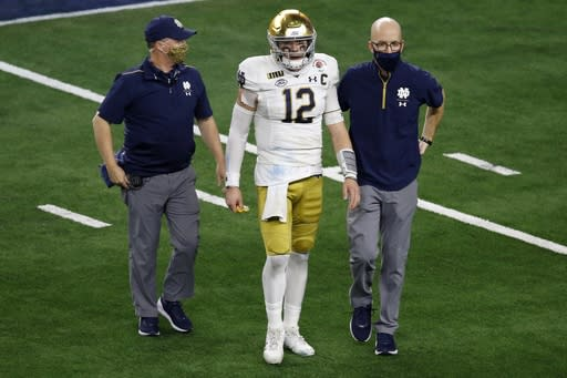 Notre Dame quarterback Ian Book is helped off the field by team medical personnel in the second half of the Rose Bowl NCAA college football game against Alabama in Arlington, Texas, Friday, Jan. 1, 2021. (AP Photo/Roger Steinman)