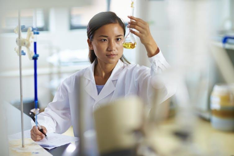 A Chinese scientist examines a flask in a laboratory.