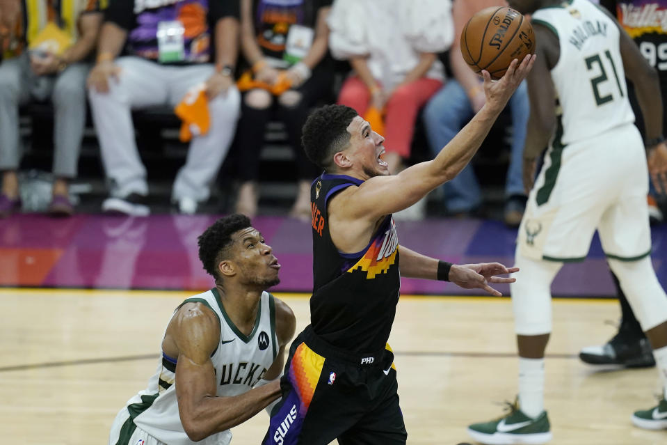 Phoenix Suns guard Devin Booker, right, shoots over Milwaukee Bucks forward Giannis Antetokounmpo during the second half of Game 5 of basketball's NBA Finals, Saturday, July 17, 2021, in Phoenix. (AP Photo/Ross D. Franklin)