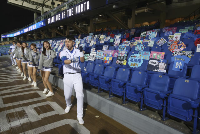 Cheerleaders encourage on the Stadium stands with no audience at Xinzhuang Baseball Stadium in New Taipei City, Taiwan, Friday, April 24, 2020. Taiwan's five-team Chinese Professional Baseball League is barring spectators over concerns they would spread the deadly coronavirus, meaning games are played with plastic seats void of fans.(AP Photo/Chiang Ying-ying)