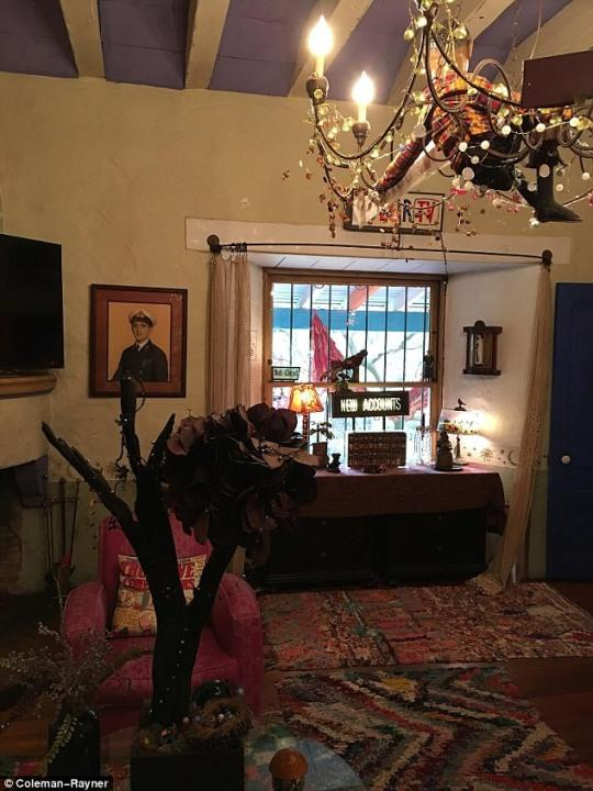 The living room is cozy and eclectic, crowned by a chandelier that cradles a gingham-shirted doll and draped strings of lights. Vibrant shag rugs and a fuschia armchair (accessorized by a cool graphic pillow) make the space inviting, and antique-looking figurines, lamps and art infuse it with even more charm.