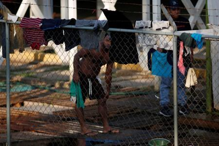 Central American migrants clean themselves in an immigration facility in Ciudad Hidalgo
