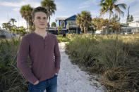Gus Bayard stands behind his family's house, two days before he leaves home for college, Friday, Jan. 8, 2021, in Anna Maria Island, Fla. The start of Bayard's freshman year at Brown University was delayed until January because of the coronavirus pandemic. (AP Photo/Steve Nesius)