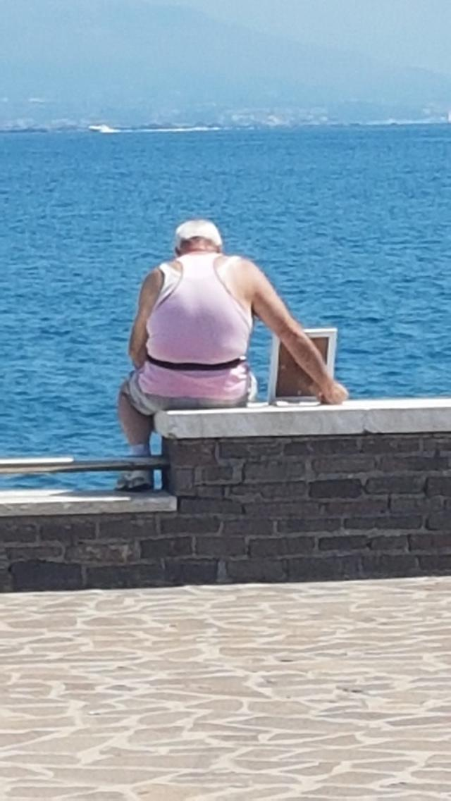A 72-year-old widower has taken his wife's portrait to the pier where they fell in love every morning since she died seven years ago. (Photo: Giorgio Moffa)