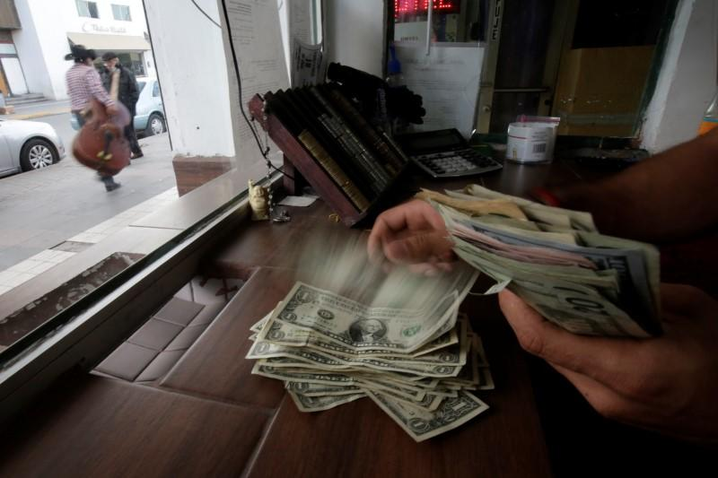 The employee of a currency exchange shop counts U.S. dollar banknotes, in Ciudad Juarez