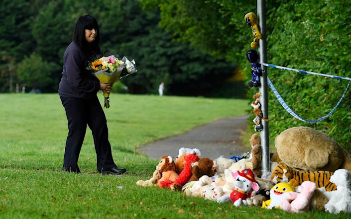 A woman laying flowers near the river where the boy was found - Wales News