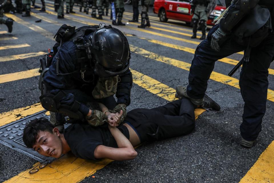 """Police detain a demonstrator during a flash mob protest in the Central district in Hong Kong on November 13, 2019. - Pro-democracy protesters stepped up on November 13 a """"blossom everywhere"""" campaign of road blocks and vandalism across Hong Kong that has crippled the international financial hub this week and ignited some of the worst violence in five months of unrest. (Photo by DALE DE LA REY / AFP) (Photo by DALE DE LA REY/AFP via Getty Images)"""
