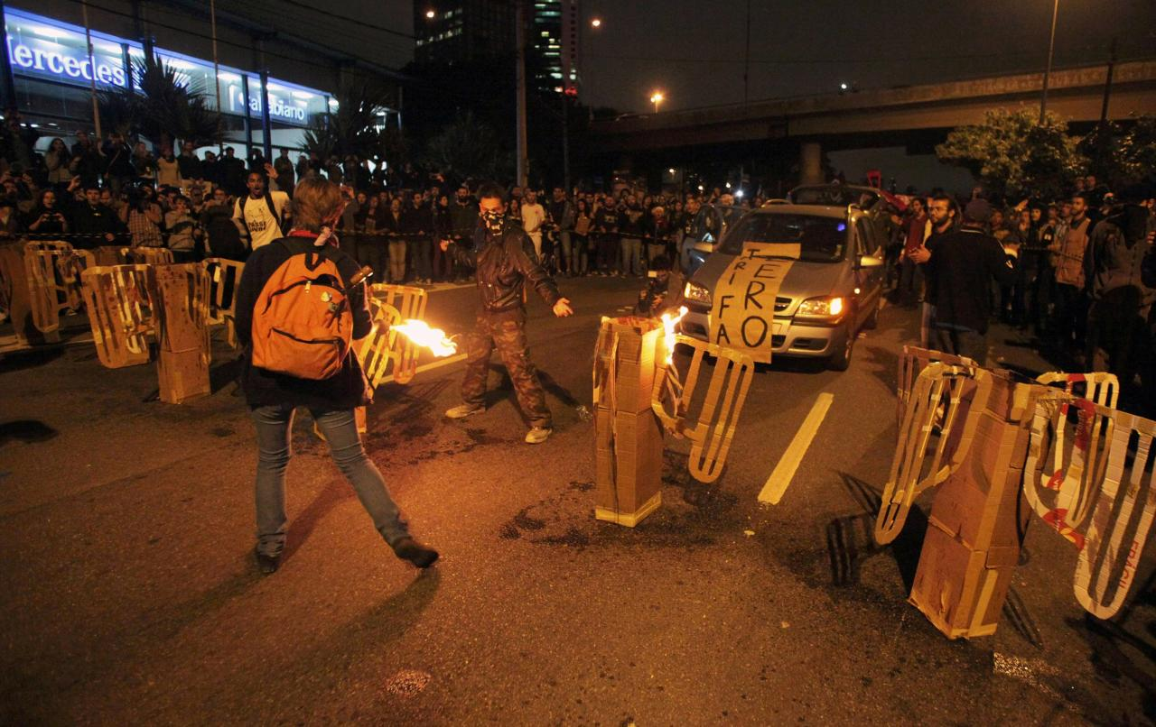 Demonstrators for free public transportation set fire to mock subway turnstiles while blocking a road in protest against the 2014 World Cup, in Sao Paulo June 19, 2014. REUTERS/Stringer/Brazil/Chico Ferreira (BRAZIL - Tags: POLITICS SOCCER SPORT TRANSPORT CIVIL UNREST WORLD CUP)