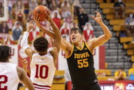 Indiana guard Rob Phinisee (10) and Iowa center Luka Garza (55) battle for the ball during the first half of an NCAA college basketball game, Sunday, Feb. 7, 2021, in Bloomington, Ind. (AP Photo/Doug McSchooler)