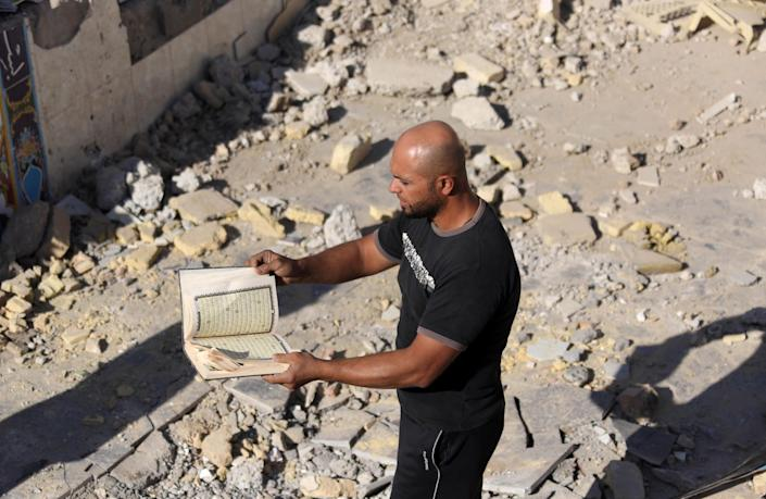 FILE - In this Sept. 30, 2013 file photo, a man inspects a copy of the Quran, Islam's holy book, amid the ruins of the al-Hussein Shiite mosque a day after a suicide bomber struck in Musayyib, about 40 miles (60 kilometers) south of Baghdad, Iraq, Al-Qaida has come roaring back in Iraq since U.S. troops left in late 2011 and now looks stronger than it has in years. The terror group is capable of carrying out mass-casualty attacks several times a month, driving the death toll in Iraq to the highest level in half a decade. It sees each attack as a way to maintain an atmosphere of chaos that weakens the Shiite-led government's authority. (AP Photo/Hadi Mizban, File)