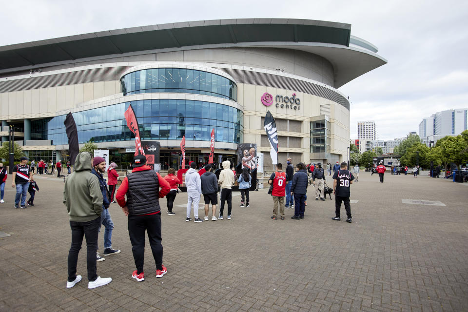 Fans line up outside Mora Center before Game 3 of an NBA basketball first-round playoff series between the Portland Trail Blazers and the Denver Nuggets on Thursday, May 27, 2021, in Portland, Ore. Attendance limits were raised to 8,000, the most for the stadium since the pandemic began. (AP Photo/Craig Mitchelldyer)