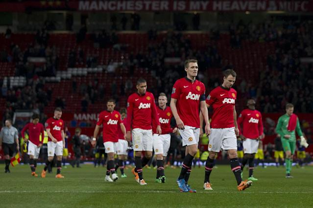 Manchester United players walk from the pitch after their 2-1 loss to Swansea City in their English FA Cup third round soccer match at Old Trafford Stadium, Manchester, England, Sunday Jan. 5, 2014. (AP Photo/Jon Super)
