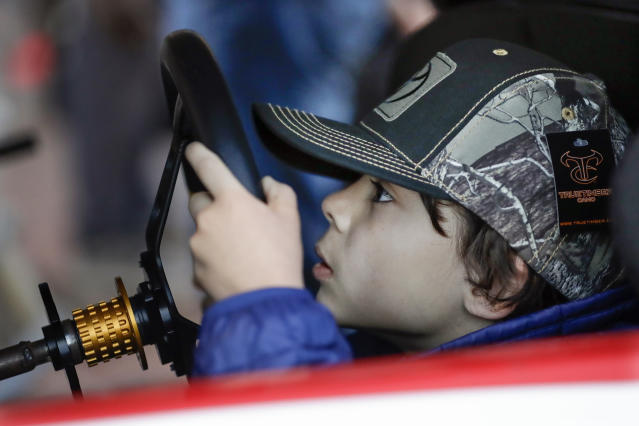 Noah Michel, 8, of Los Angeles, peeks through the steering wheel as he drives a racing simulator Wednesday, Dec. 4, 2019, during NASCAR Champion's Week in Nashville, Tenn. (AP Photo/Mark Humphrey)