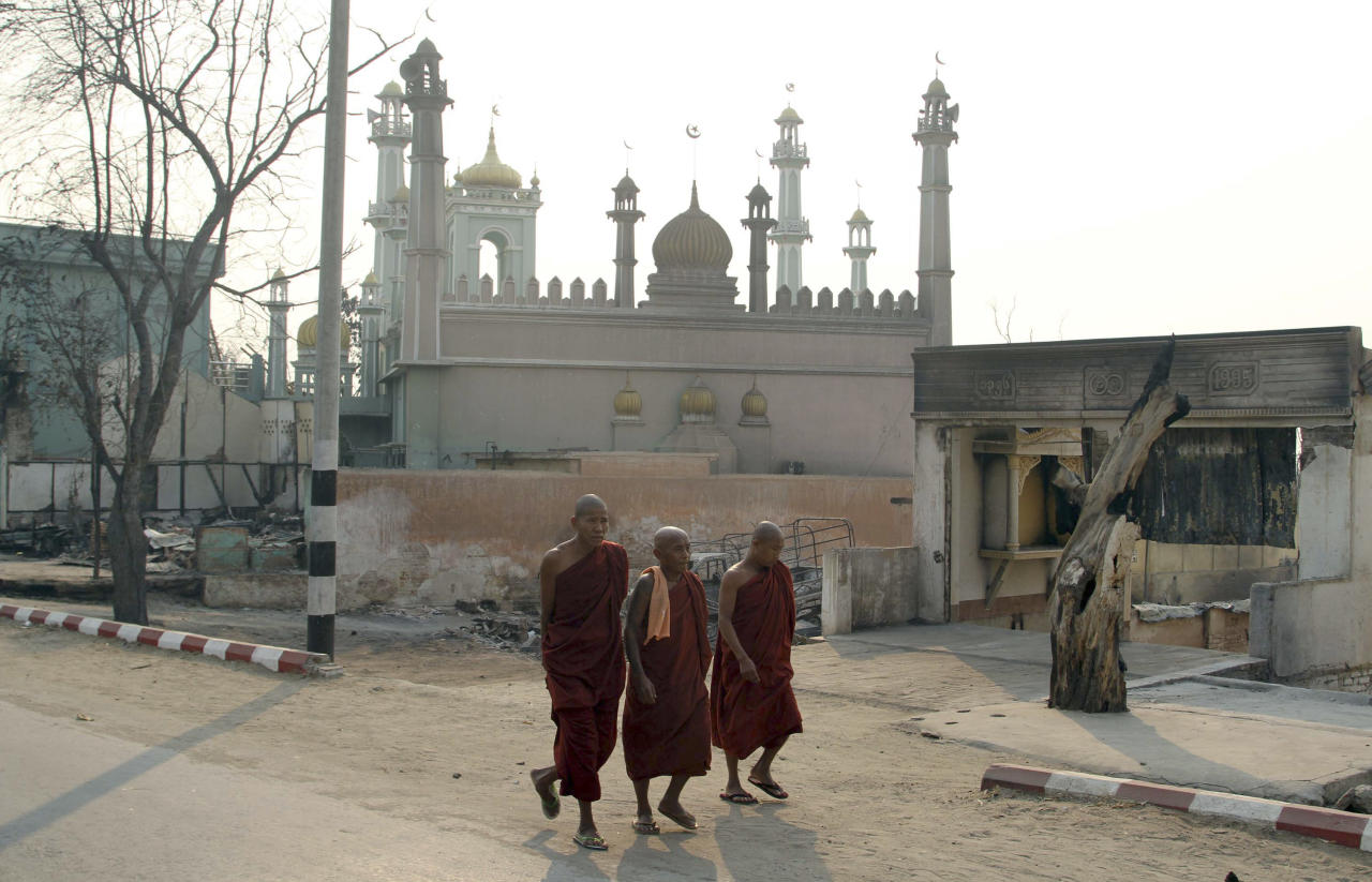 Three Buddhist monks walk on a road near a mosque in Meikhtila, about 550 kilometers (340 miles) north of Yangon, Myanmar, Monday, March 25, 2013. Sectarian clashes between Buddhists and Muslims in Myanmar spread to at least two other towns in the country's heartland over the weekend, undermining government efforts to quash an eruption of violence that has killed dozens of people and displaced 10,000 more. On Sunday, Vijay Nambiar, the U.N. secretary-general's special adviser on Myanmar, toured Meikhtila, where soldiers were able to impose order after several days of anarchy and called on the government to punish those responsible. (AP Photo/Khin Maung Win)