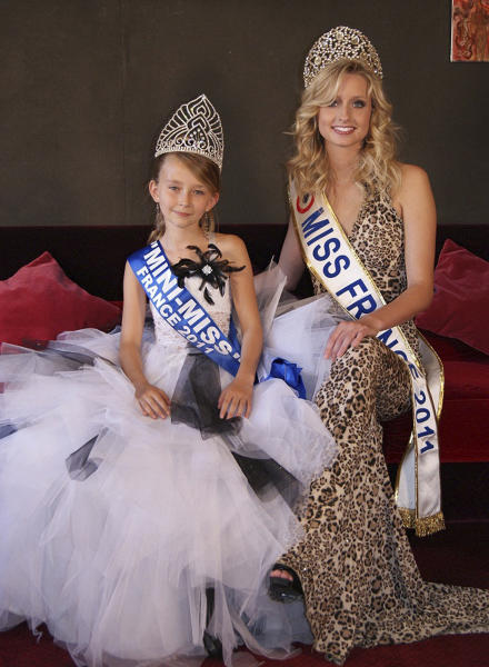 This undated photo provided by the Mini Miss committee shows Oceane Scharre, 10, elected Mini Miss France 2011, left, and Miss France 2011 Mathilde Florin. France's Senate voted Tuesday night, Sept. 17, 2013, to ban beauty pageants for children under 16, in an effort to protect children — especially girls — from being sexualized too early. Anyone who enters a child into such a contest would face up to two years in prison and 30,000 euros in fines, according to the measure. (AP Photo/Mini Miss Committee) FRANCE OUT