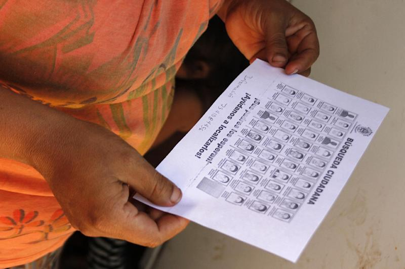 A woman holds a sheet of paper with pictures of the 43 missing students during in a search operation on the outskirts of Iguala, Guerrero State, Mexico, on January 15, 2015
