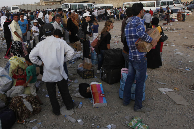 Syrian refugees wait for buses after crossing the border toward Iraq at Peshkhabour border point in Dahuk, 260 miles (430 kilometers) northwest of Baghdad, Iraq, Monday, Aug. 19, 2013. The UN High Commissioner for Refugees (UNHCR) has set up an emergency transit camp in Irbil, where around 2,000 refugees are camping out and UNHCR officials say some thousands of Syrians have been streaming into northern Iraq, many coming across a newly-constructed pontoon bridge over the Tigris River at Peshkhabour. (AP Photo/Hadi Mizban)