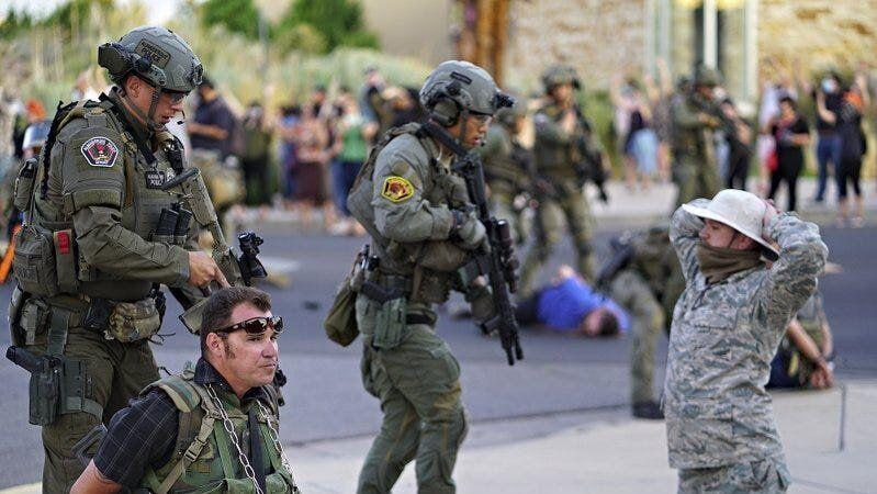 Albuquerque police detain members of the New Mexico Civil Guard, an armed civilian group, following the shooting of a man during a protest over a statue of Spanish colonial official Juan de Oñate on Monday. (Photo: Adolphe Pierre-Louis/The Albuquerque Journal via Associated Press)