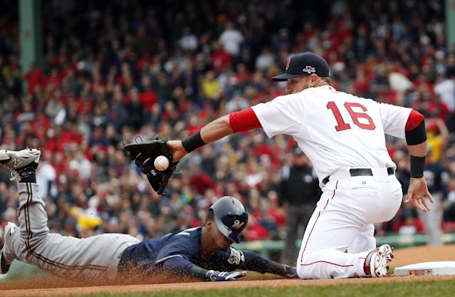 Milwaukee Brewers' Jean Segura slides in safely with a triple as Boston Red Sox third baseman Will Middlebrooks (16) takes in the throw from left field during the first inning of a baseball game at Fenway Park in Boston, Friday, April 4, 2014. (AP Photo/Elise Amendola)