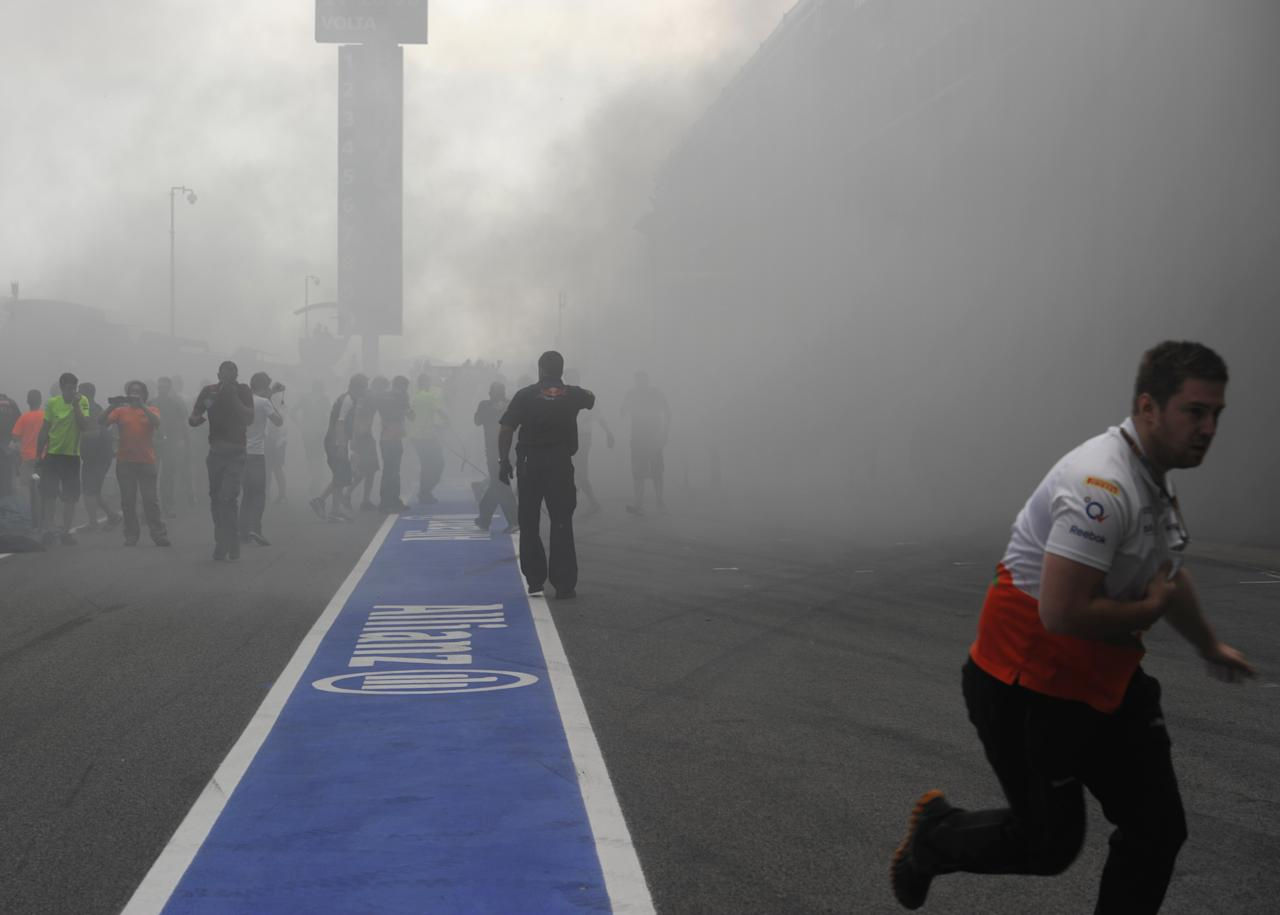 Racing team crews run to help extinguish a fire in the Williams racing pit stand at the Circuit de Catalunya on May , 2012 in Montmelo on the outskirts of Barcelona after the Spanish Formula One Grand Prix.   AFP PHOTO / DIMITAR DILKOFFDIMITAR DILKOFF/AFP/GettyImages