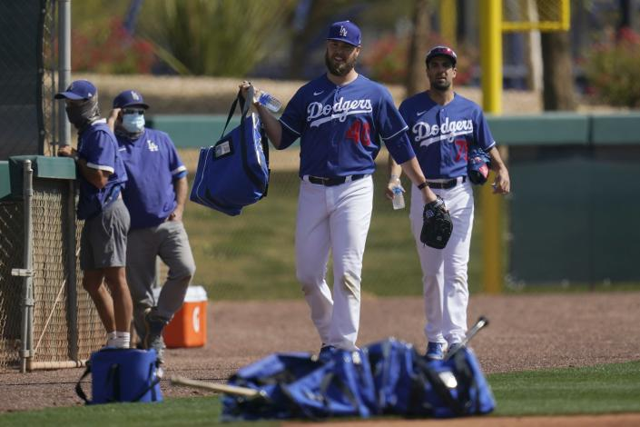 Los Angeles Dodgers pitchers Jimmy Nelson and Scott Alexander (75) make their way on to a new practice field during a spring training baseball practice Tuesday, Feb. 23, 2021, in Phoenix. (AP Photo/Ross D. Franklin)