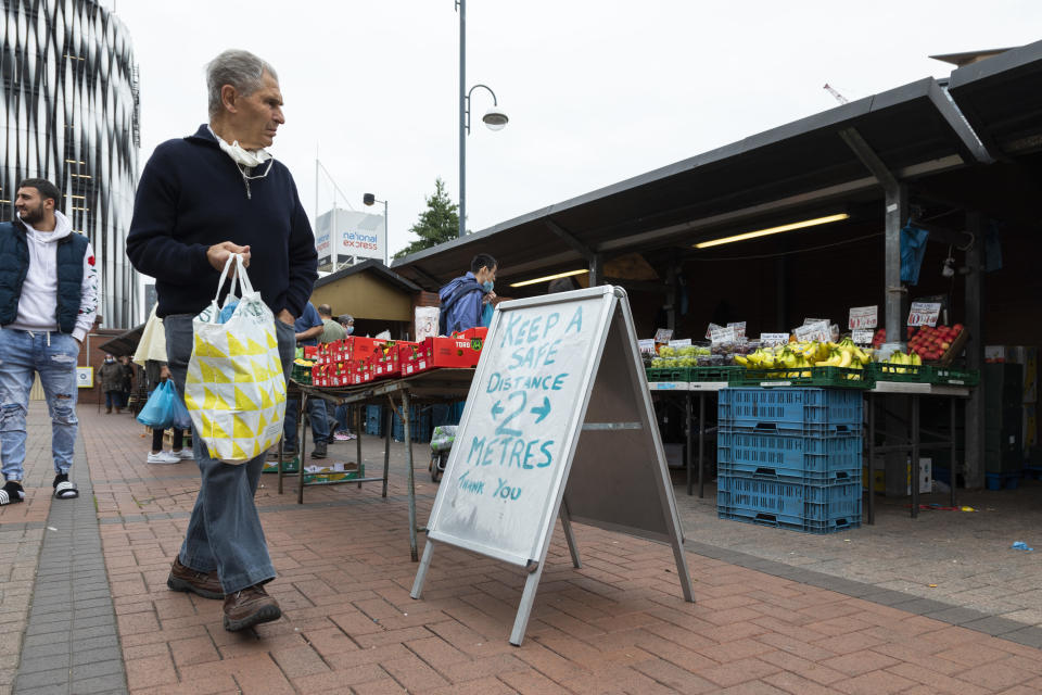 A man holding a shopping bag passes a Covid-19 social distancing sign as he browses fresh fruit and vegetables at the outdoor market on 4th September, 2021 in Leeds, United Kingdom. A combination of Brexit and Covid-19 is reportedly exacerbating an already severe staff shortage in the British food industry, with a lack of fruit and vegetable pickers that could see a hike in food prices across the country. (photo by Daniel Harvey Gonzalez/In Pictures via Getty Images)