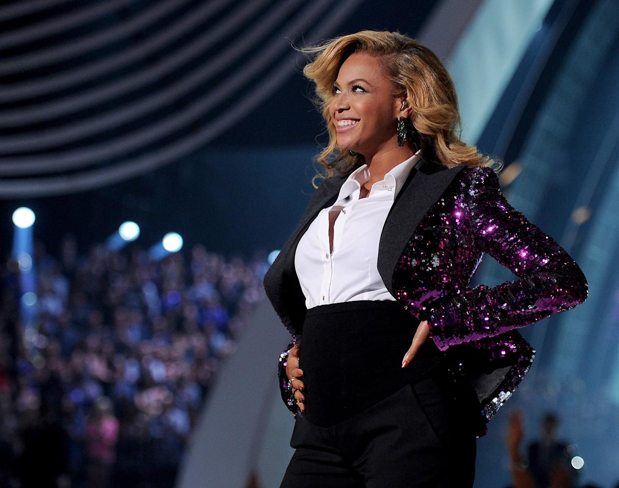 """<p>After first <a href=""""&lt;br%20/&gt;%0Ahttps://www.popsugar.com/entertainment/Pregnant-Beyonce-Knowles-Performing-2011-VMA-Video-18902838"""" class=""""ga-track"""" data-ga-category=""""Related"""" data-ga-label=""""&lt;br /&gt; https://www.popsugar.com/entertainment/Pregnant-Beyonce-Knowles-Performing-2011-VMA-Video-18902838"""" data-ga-action=""""In-Line Links"""">revealing her pregnancy</a> at the 2011 MTV Video Music Awards red carpet, Beyoncé showed off her bump again during her performance of """"Love on Top."""" She unbuttoned her embellished jacket to rub her belly and the moment forever went down. </p>"""