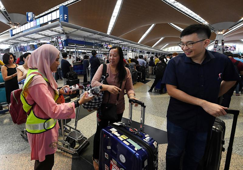 A MAHB member of staff distributes water and snacks to passengers at KLIA in Sepang August 23, 2019. — Bernama pic