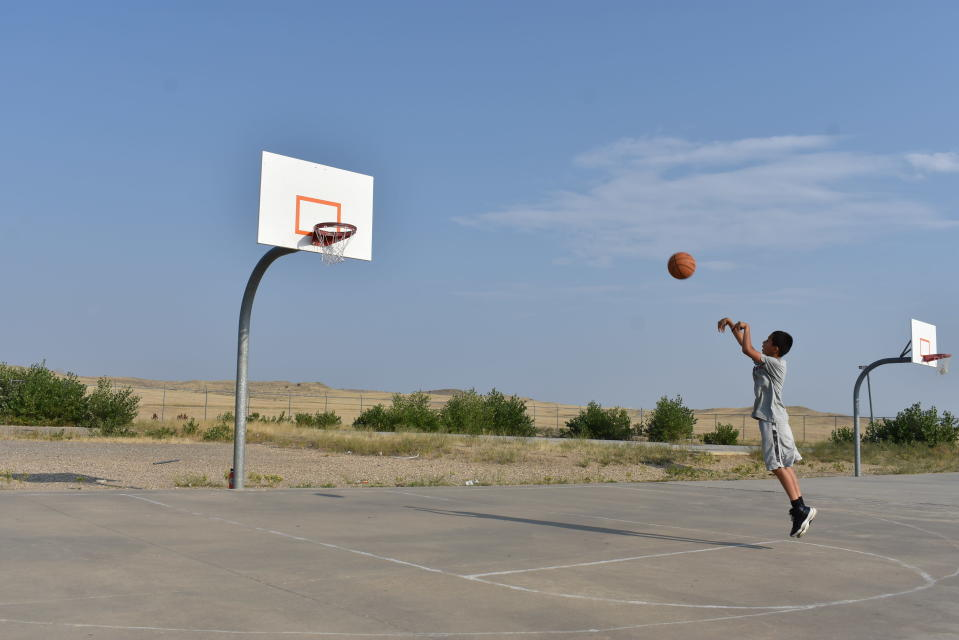 Julian Nomee, 14, shoots a basketball at a court on the Crow Indian Reservation near Crow Agency, Mont. on Wednesday, Aug. 26, 2020. U.S. Census officials are struggling to get an accurate count of households on the reservation that covers an area bigger than Delaware with a population of about 8,000 people. (AP Photo/Matthew Brown)