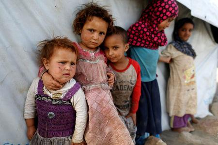 Children stand next to a tent at a camp for people displaced by the war near Sanaa, Yemen