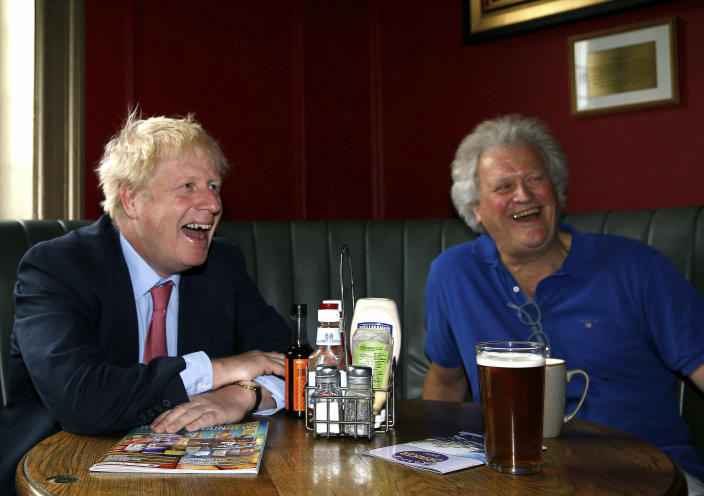 Conservative Party leadership candidate Boris Johnson, left, reacts with Tim Martin, Chairman of JD Wetherspoon, during a visit to Wetherspoons Metropolitan Bar in London, Wednesday July 10, 2019. (Henry Nicholls/Pool Photo via AP)