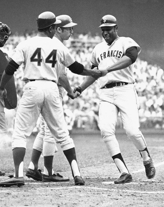 "FILE - In this July 23, 1969, file photo, National League's Willie McCovey of San Francisco is congratulated on crossing home in the third inning of the baseball All-Star Game in Washington after hitting in Hank Aaron (44) in Washington. McCovey hit another home in the next inning. Also shaking his hand is Ron Santo, on deck. McCovey, the sweet-swinging Hall of Famer nicknamed ""Stretch"" for his 6-foot-4 height and those long arms, has died. He was 80. The San Francisco Giants announced his death, saying the fearsome hitter passed peacefully Wednesday afternoon, Oct. 31, 2018, after losing his battle with ongoing health issues. (AP Photo, File)"