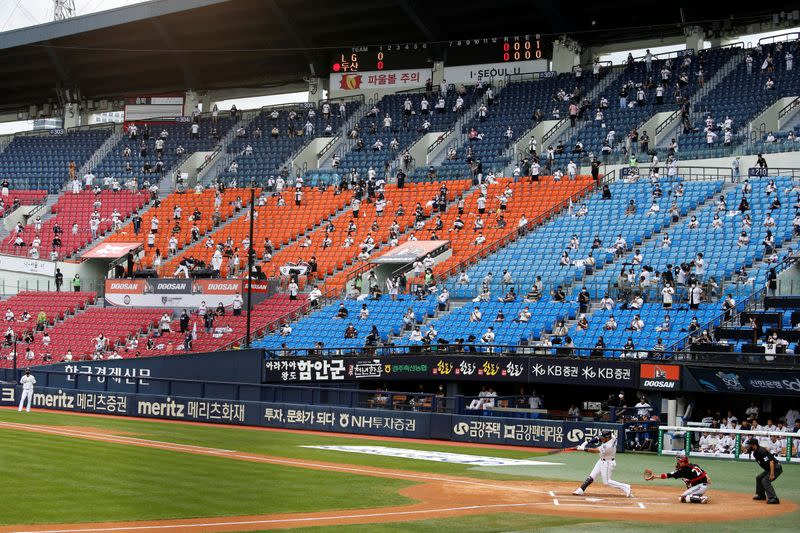 Socially-distanced fans wearing face masks as a measure to avoid the spread of the coronavirus disease (COVID-19), watch a KBO baseball game between LG Twins and Doosan Bears at a baseball stadium in Seoul