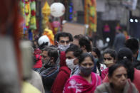 Indians wearing face masks as a precautionary measure against the coronavirus crowd a market during Diwali, the Hindu festival of lights, in Jammu, India, Saturday, Nov. 14, 2020. (AP Photo/ Channi Anand)