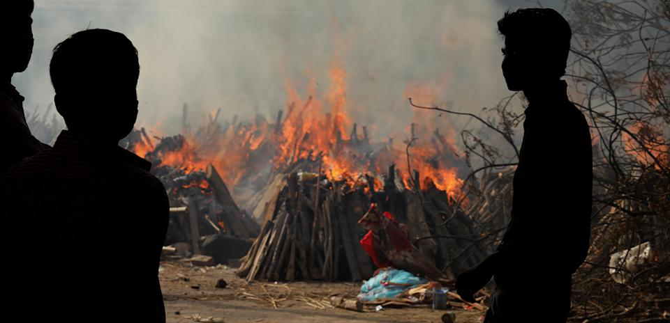 Family members look on as several funeral pyres of patients who died of Covid-19 burn up during a mass cremation in New Delhi. Source: Getty