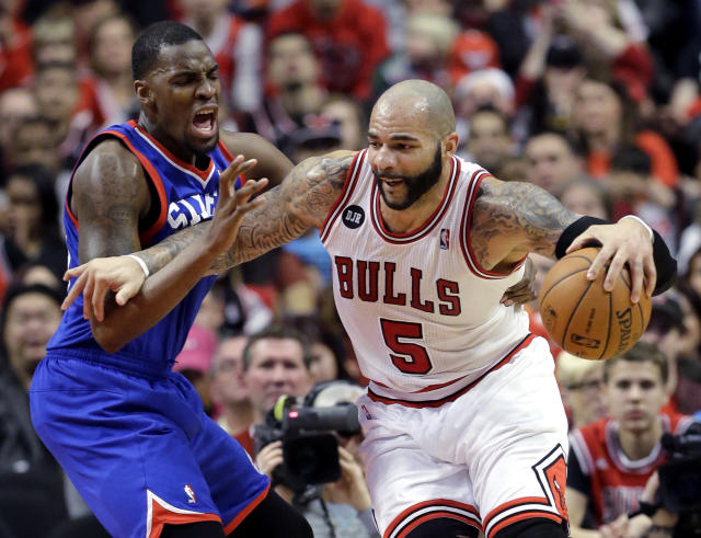 Chicago Bulls forward Carlos Boozer, right, drives against Philadelphia 76ers forward Jarvis Varnado during the first half of an NBA basketball game in Chicago on Saturday, March 22, 2014. (AP Photo/Nam Y. Huh)